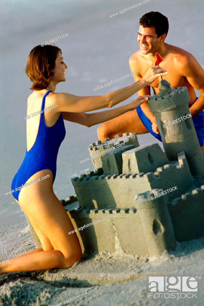 Stock Photo: Young couple making a sand castle on the beach.