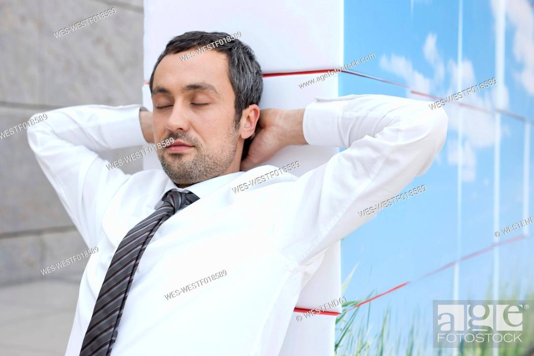 Stock Photo: Germany, Leipzig, Businessman resting on cubes.