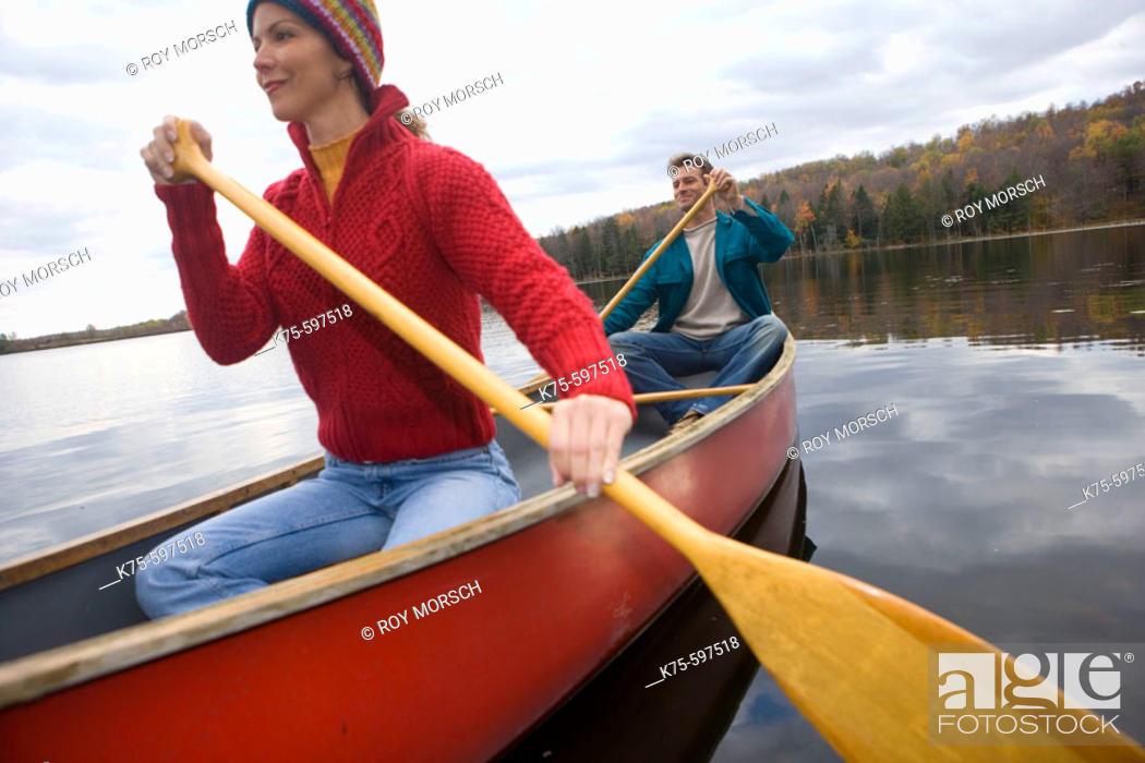 Stock Photo: Couple canoe on lake in the fall.