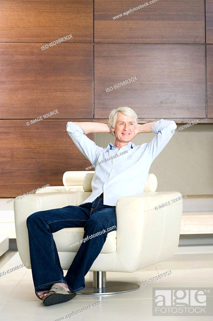 Stock Photo: Middle aged man relaxing in modern armchair.