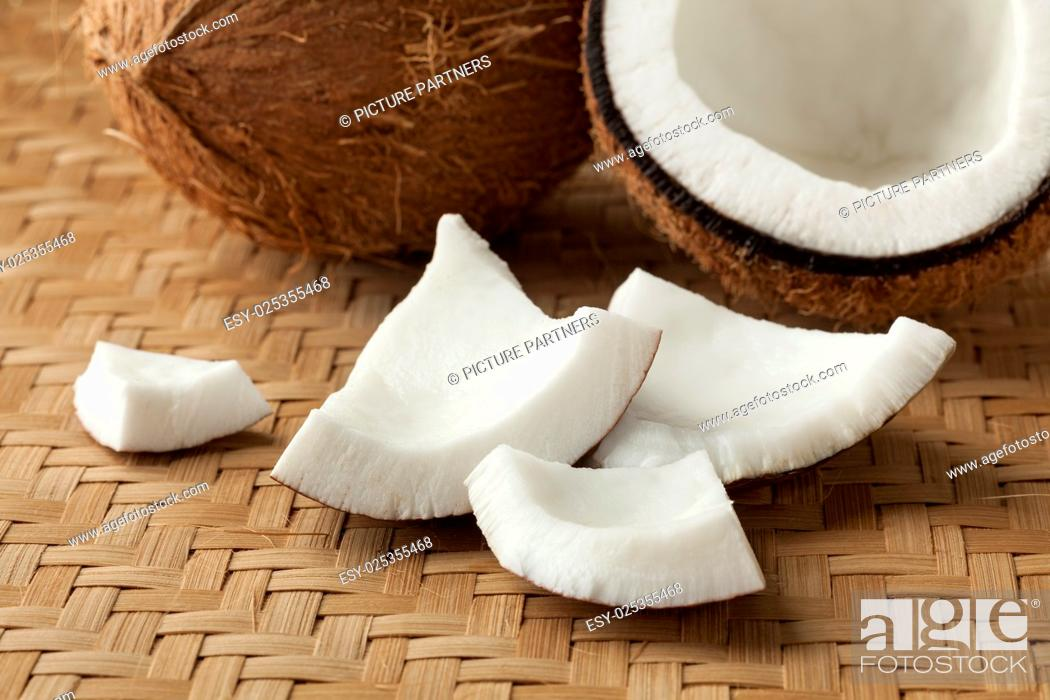 Photo de stock: Cracked fresh coconut with pieces.