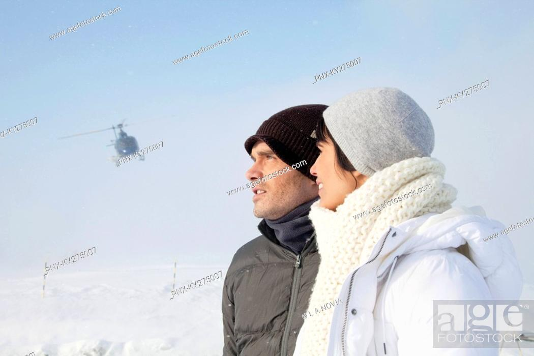 Stock Photo: Young couple in winter clothes, helicopter in background.