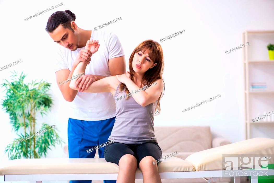 Stock Photo: The young woman visiting male doctor physiotherapist.