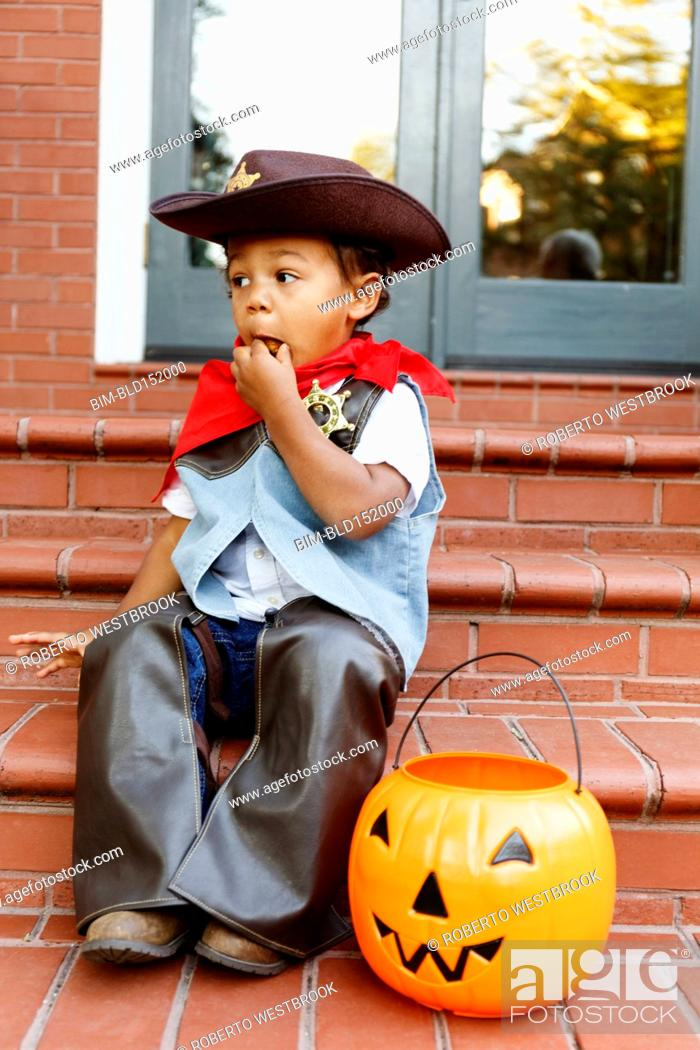 Stock Photo: Mixed race boy dressed as cowboy eating Halloween candy.