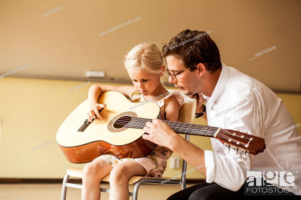 Stock Photo: Male teacher teaching girl to play guitar.