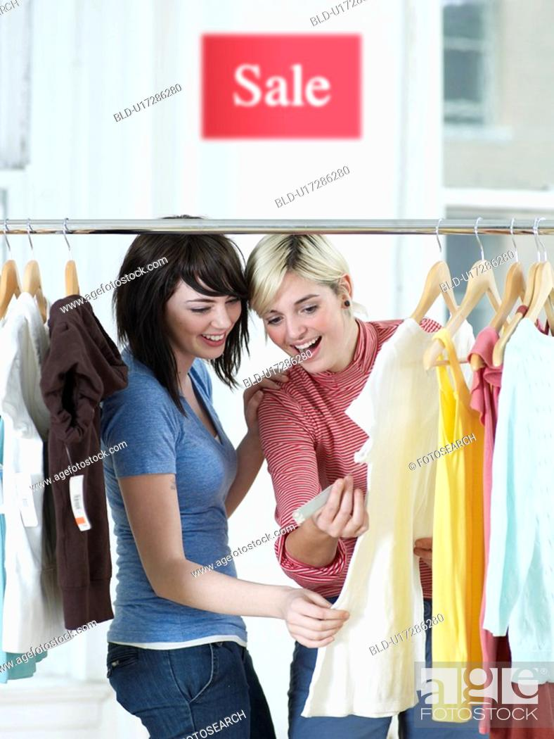 Stock Photo: Young Women Looking at Price Tag of T-Shirt.