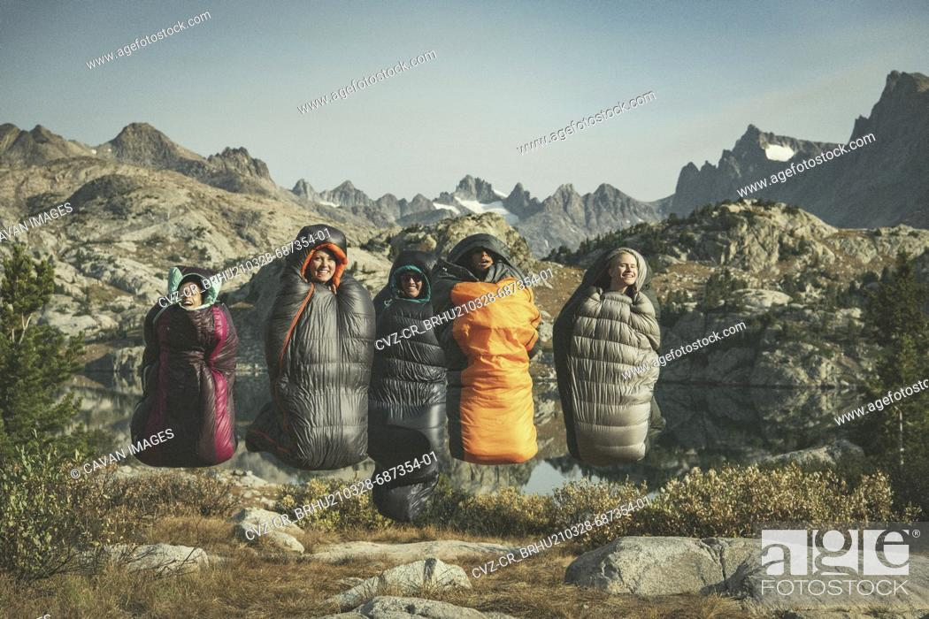 Stock Photo: Carefree female friends jumping with sleeping bags against mountain range while enjoying vacation.