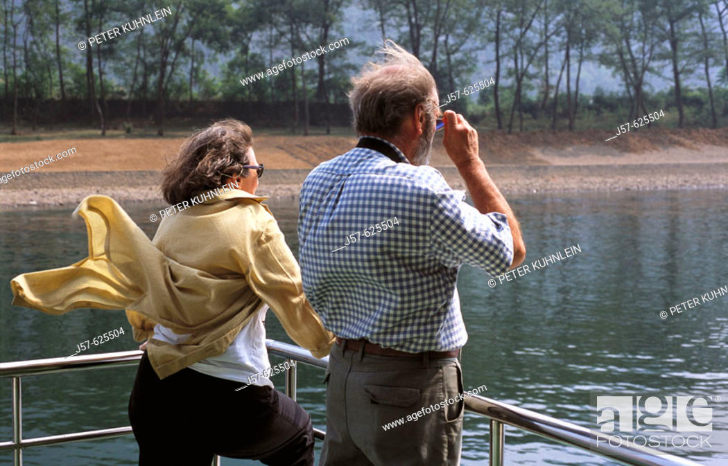 Stock Photo: Tourist looking at mountains from boat on river, Guilin. China.