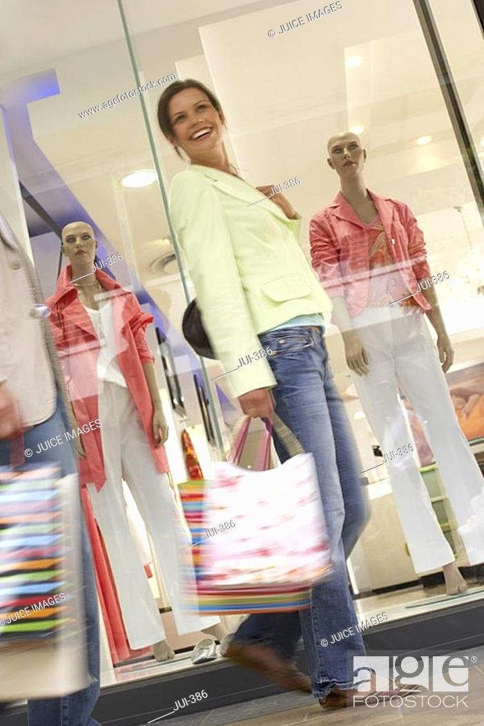 Stock Photo: Couple with shopping bags walking past window display in shop, low angle view blurred motion, tilt.