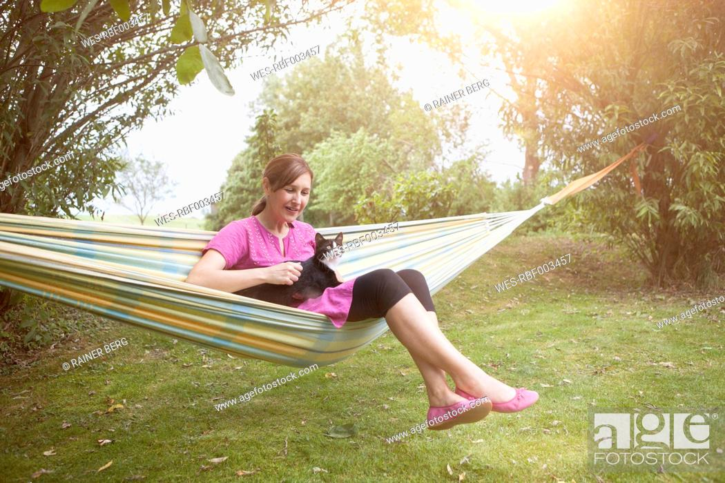Stock Photo: Relaxed woman with cat in hammock.