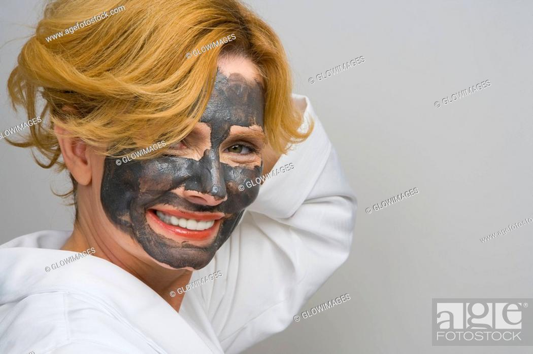 Stock Photo: Portrait of a mature woman wearing facial masks and smiling.
