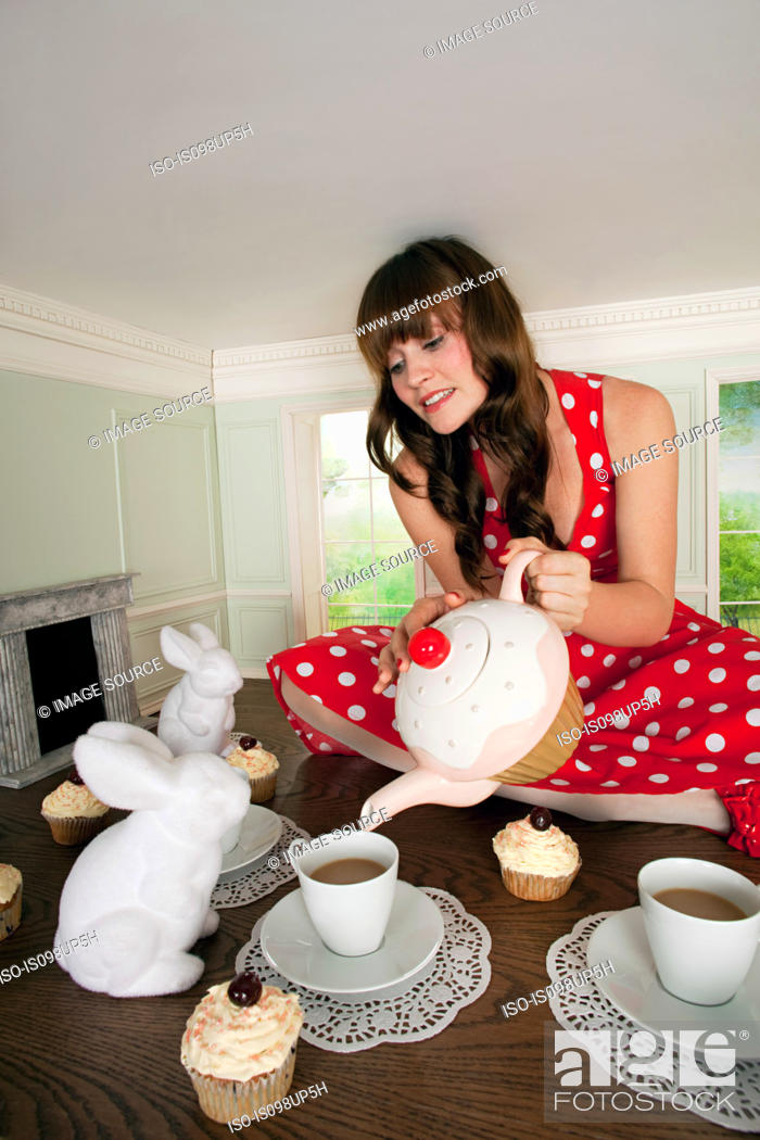 Stock Photo: Young woman having tea party in small room.