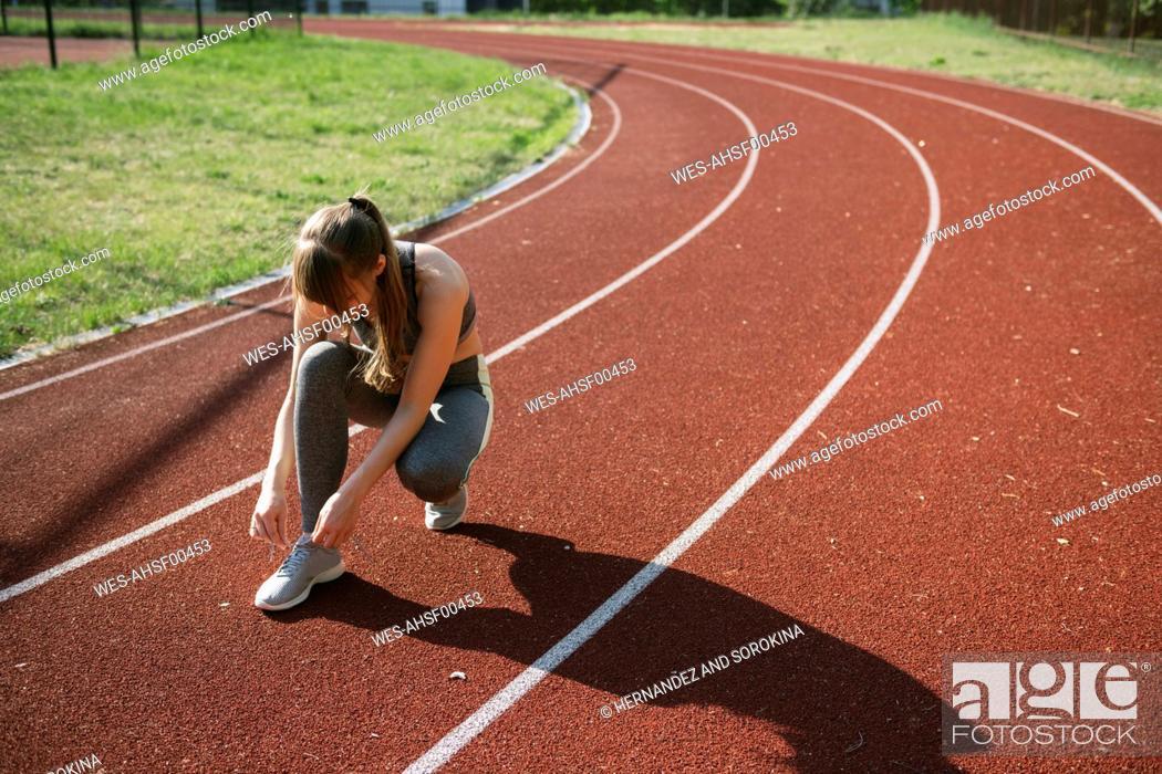 Photo de stock: Sportswoman on racetrack tying shoes.
