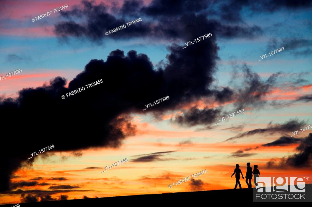 Stock Photo: Silhouettes of three girls walking in the sunset.