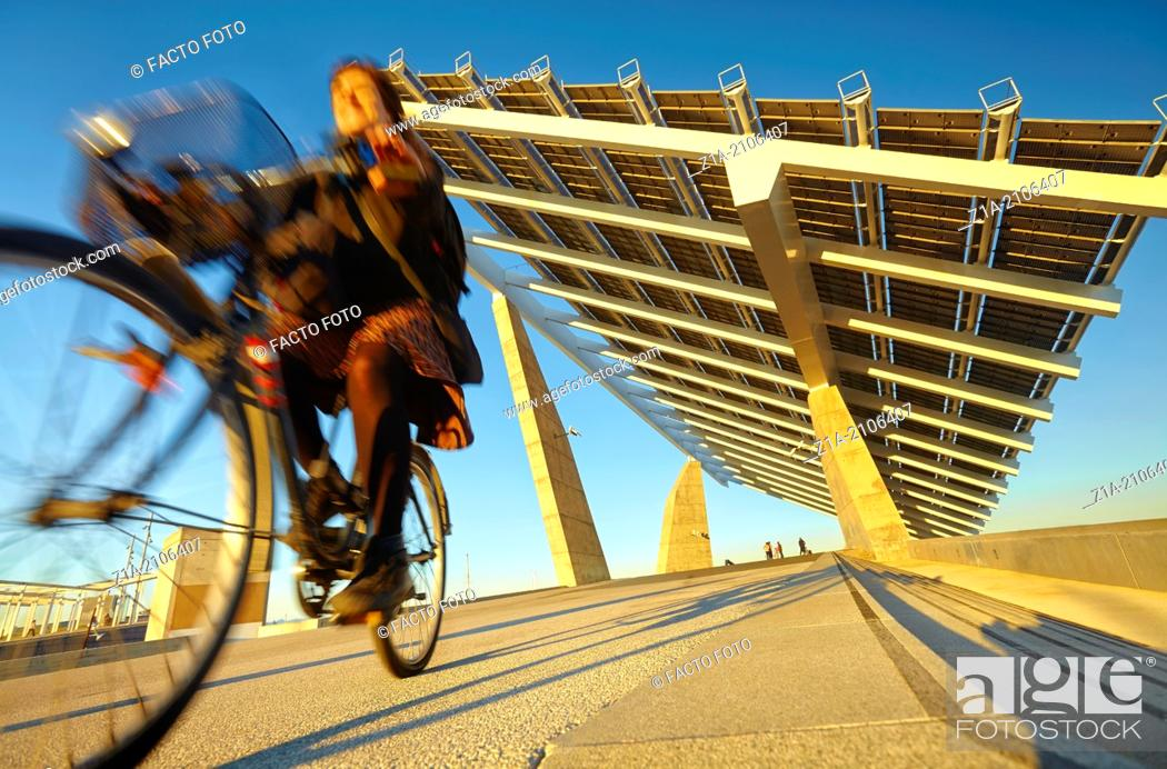 """Imagen: Cyclist passing by the solar panels at the Forum Esplanade, designed by architects Elias Torres and Jose Antonio Martinez Lapena for the """"""""Forum Barcelona."""
