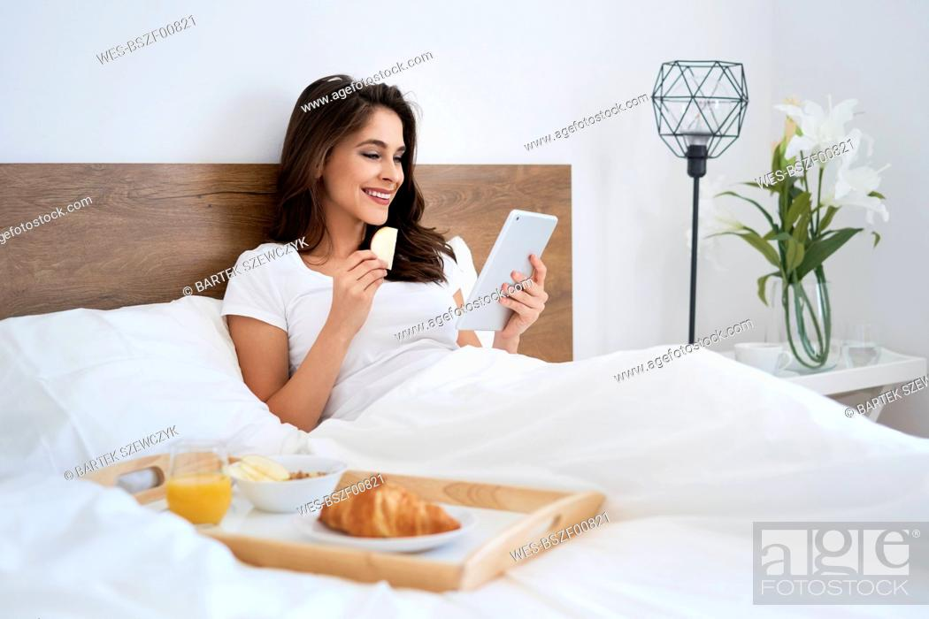 Stock Photo: Young woman having breakfast in bed, using digital tablet, reading.