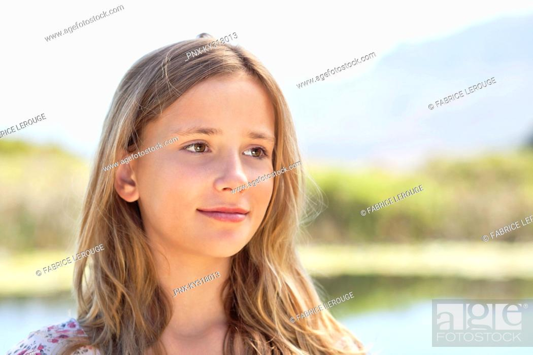 Stock Photo: Close-up of smiling girl day dreaming.