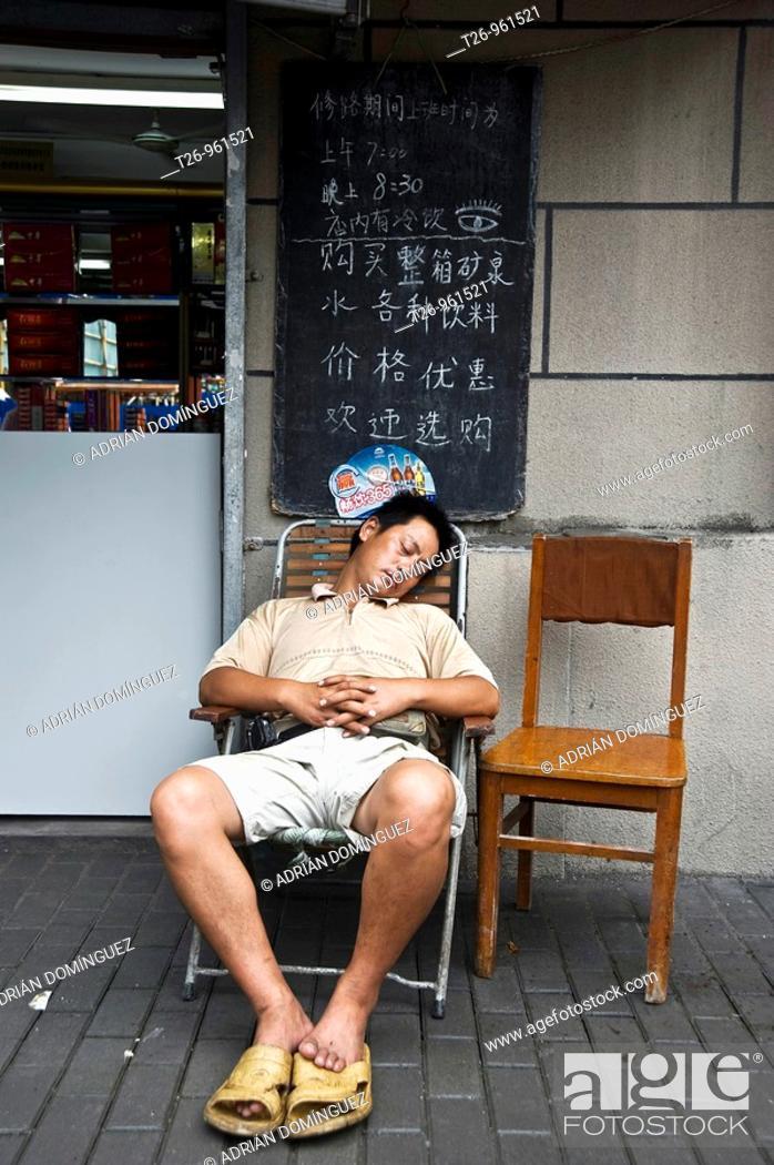 Stock Photo: a man sleeping in a chair. Shanghai, China.