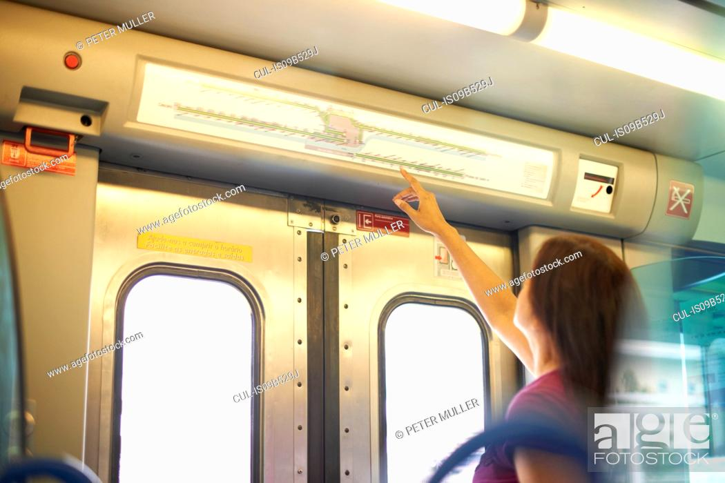 Stock Photo: Woman pointing to station map in train carriage.