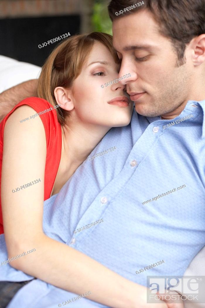 Stock Photo: Couple relaxing in living room where the man is sleeping.