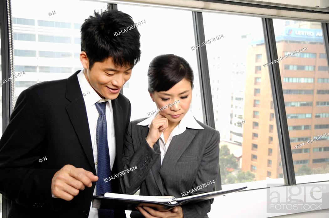Stock Photo: Business executives discussing a file in an office.