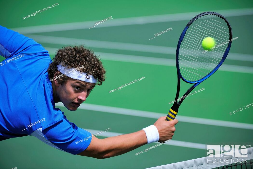Stock Photo: Male tennis player dives to return ball.