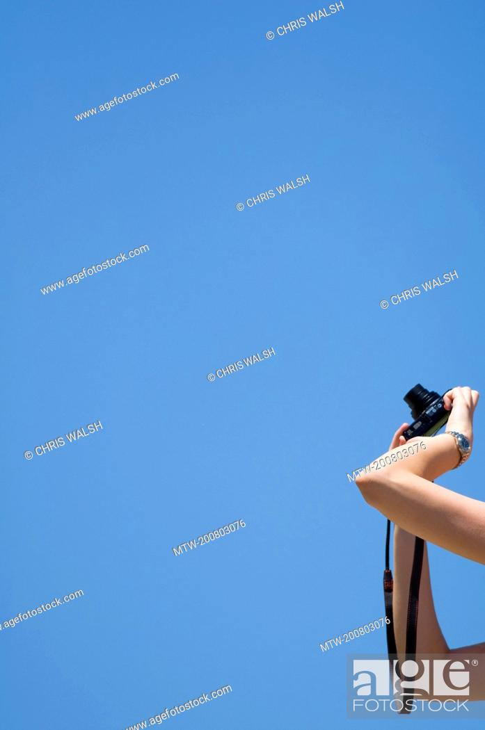 Imagen: Detail hand holding camera taking photo close up.