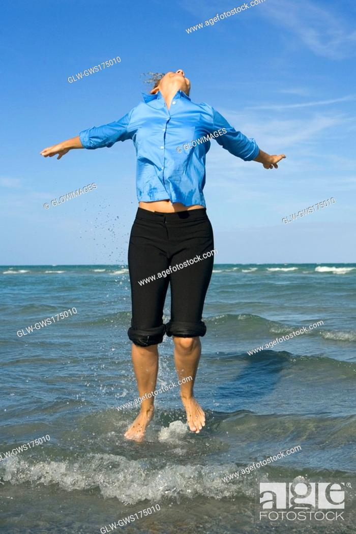 Stock Photo: Mid adult woman jumping on the beach with her arms outstretched.