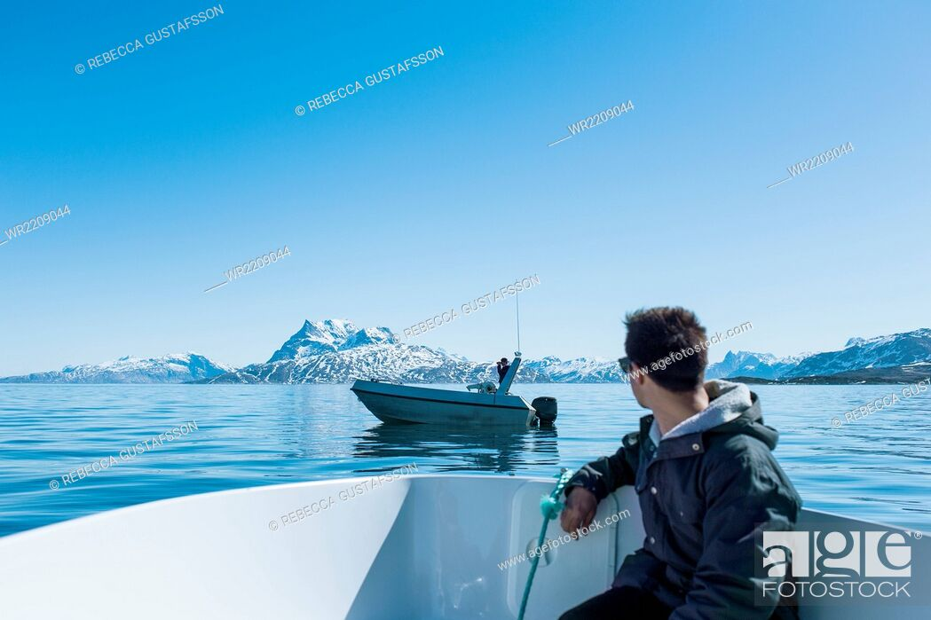 Stock Photo: Young man sitting in boat looking at snowcapped mountains.
