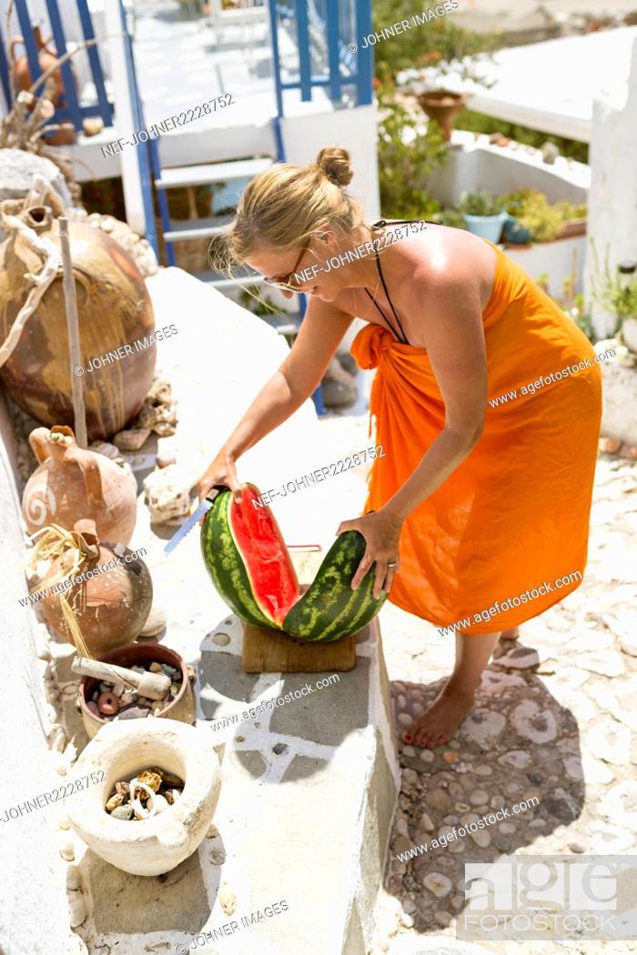 Stock Photo: Woman cutting watermelon.