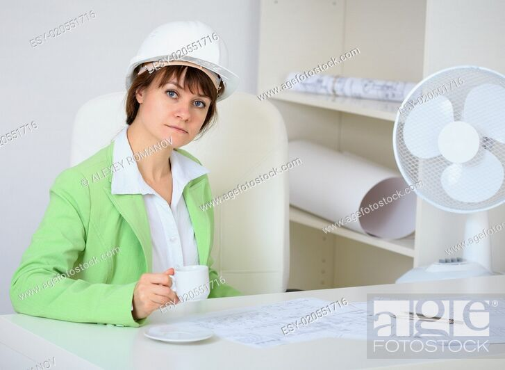 Stock Photo: Woman - a builder in helmet with cup in hand.