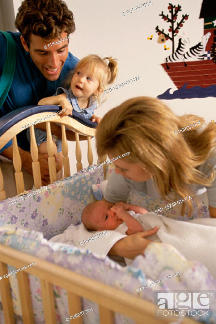 Stock Photo: Father and mother looking at their baby in a crib.