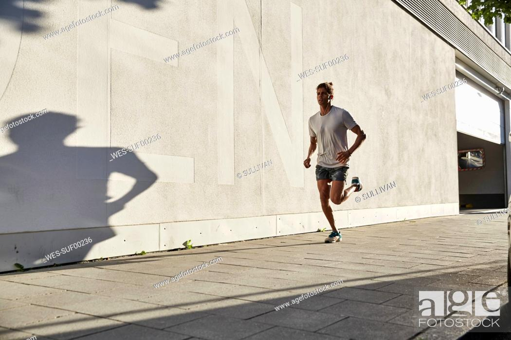 Stock Photo: Young man running in the city.