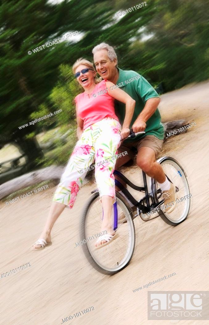 Stock Photo: Woman riding on handlebars of mans bicycle.