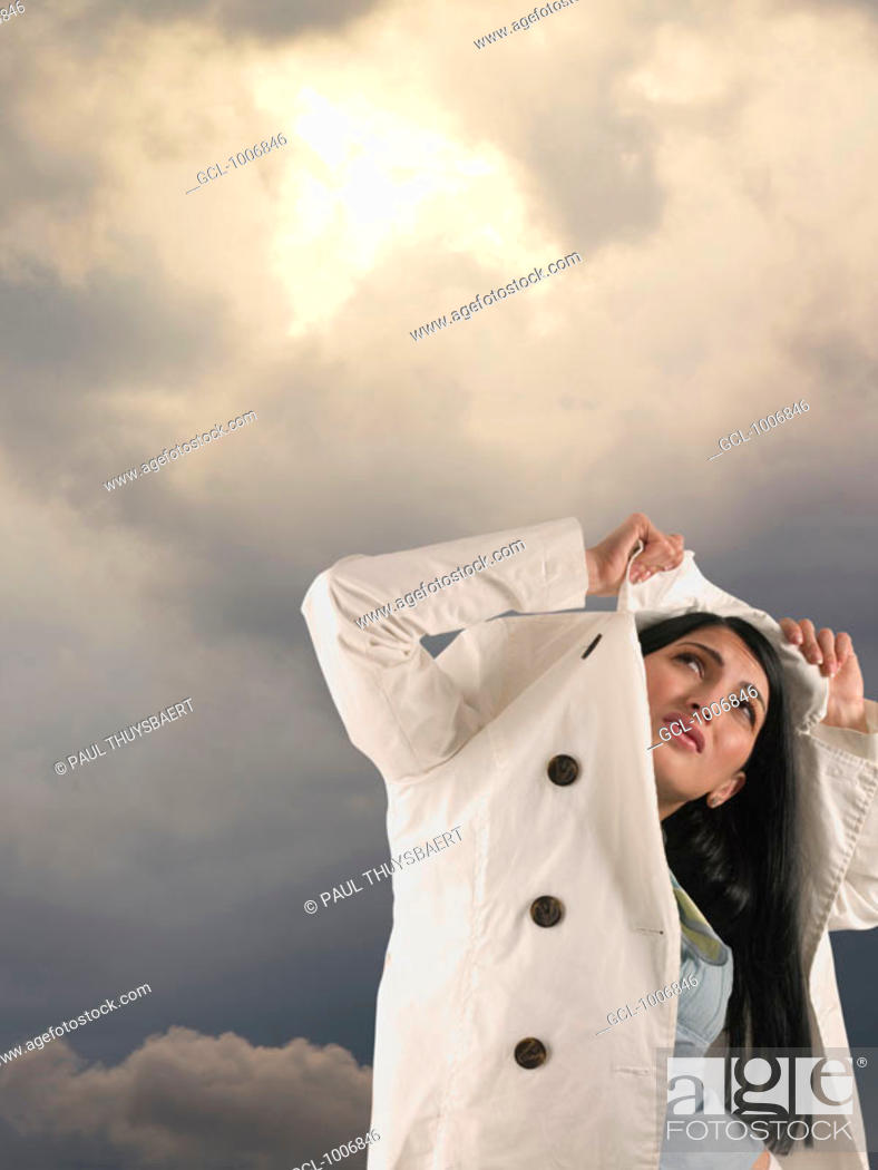 Stock Photo: Woman protecting herself with coat from rain.