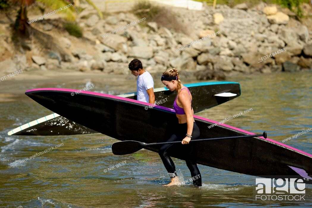 Photo de stock: Young couple with paddleboards wading in ocean.