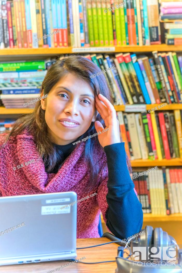Imagen: Portrait of mature female student using laptop in library.