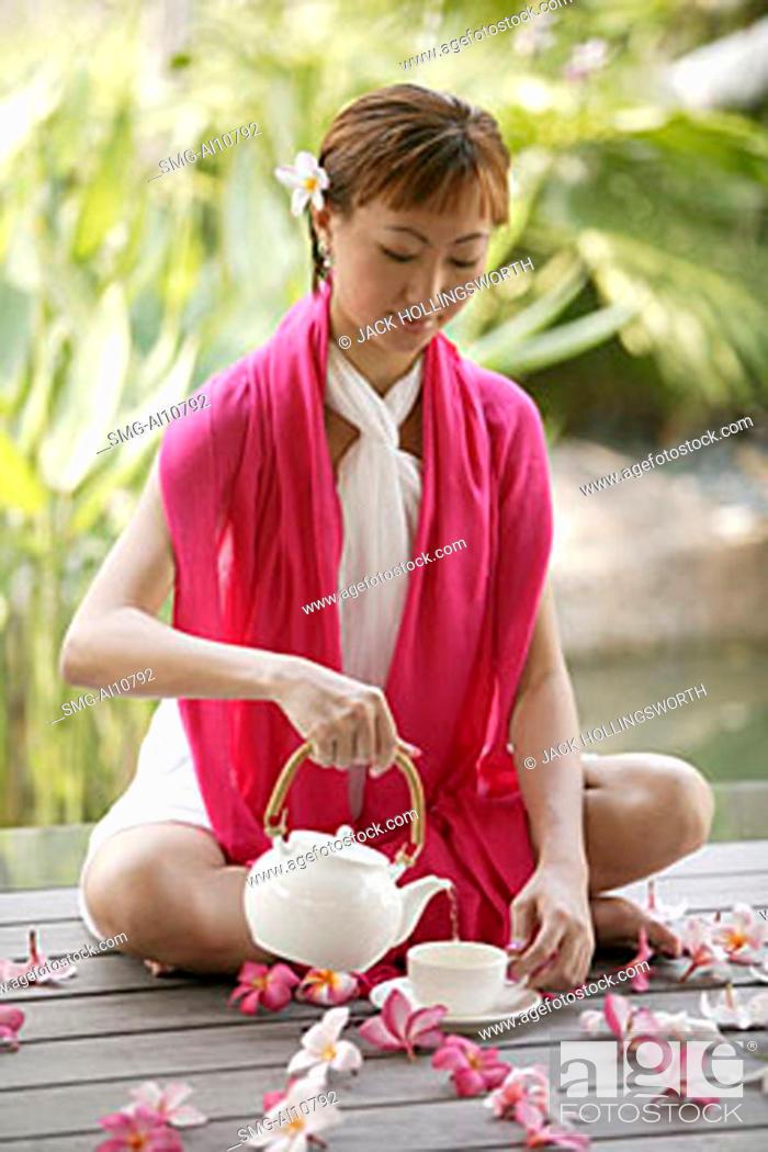 Stock Photo: Young woman pouring tea, portrait.