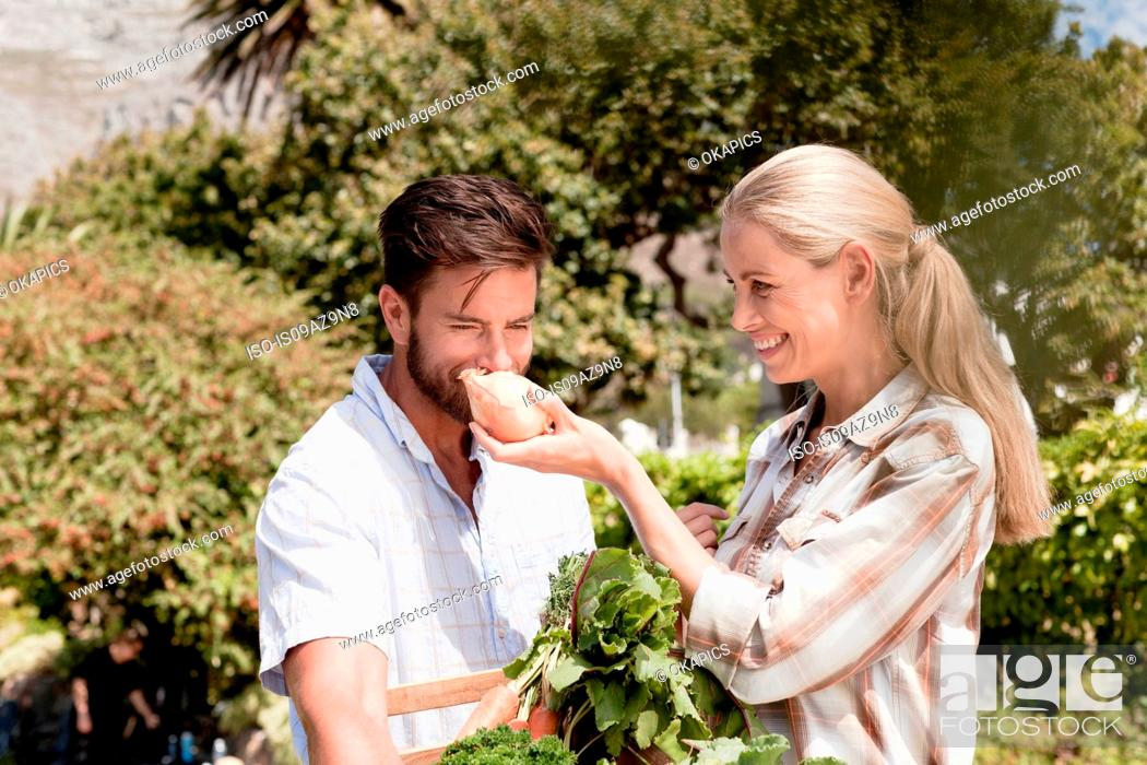 Stock Photo: Mature couple in garden, woman holding up fresh onion for man to smell.