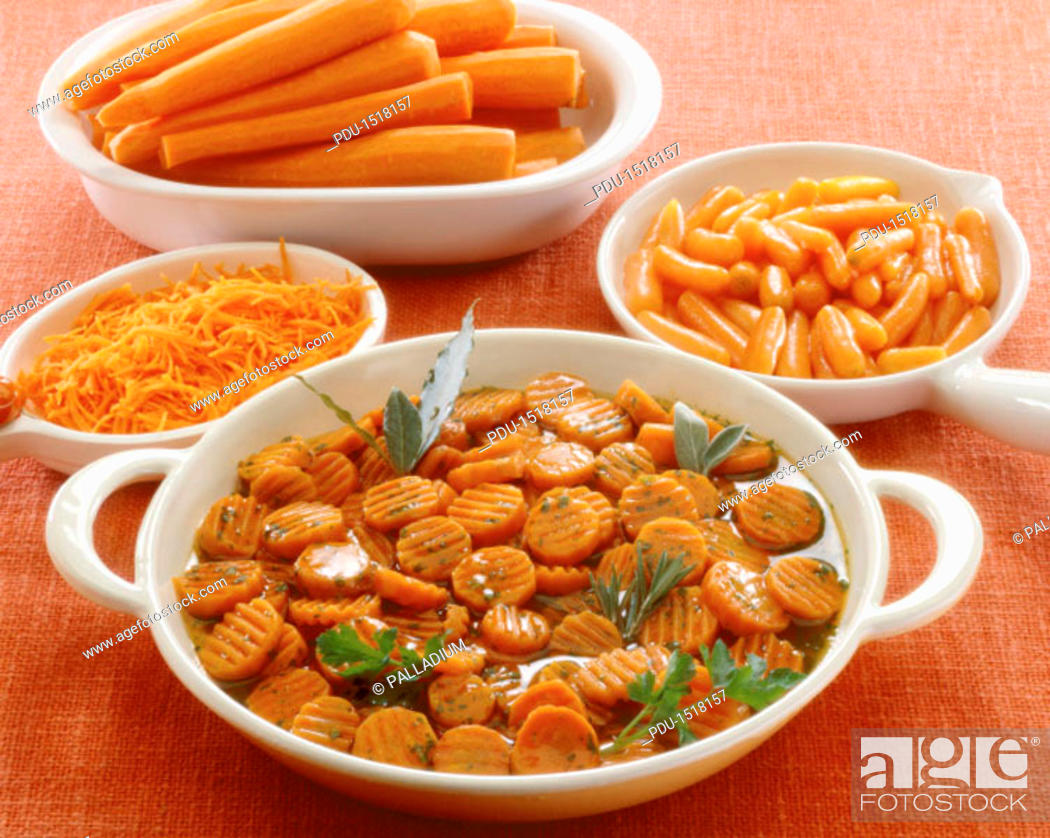 Stock Photo: high angle view of a dish of sliced carrots garnished with herbs and served on a table with grated and whole carrots.