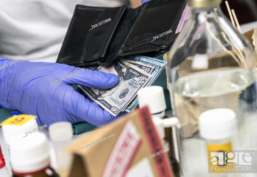 Stock Photo: Police specialist examines wallet with money from a crime scene, conceptual image.