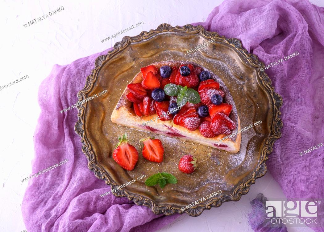 Stock Photo: half cheesecake with strawberries on a metal round plate, top view.