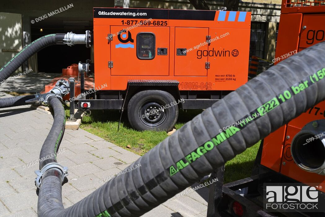 Stock Photo: A not in use red gas powered portable pump with a long hose to temporarily move sewerage at a univeristy, Toronto, Ontario, Canada.
