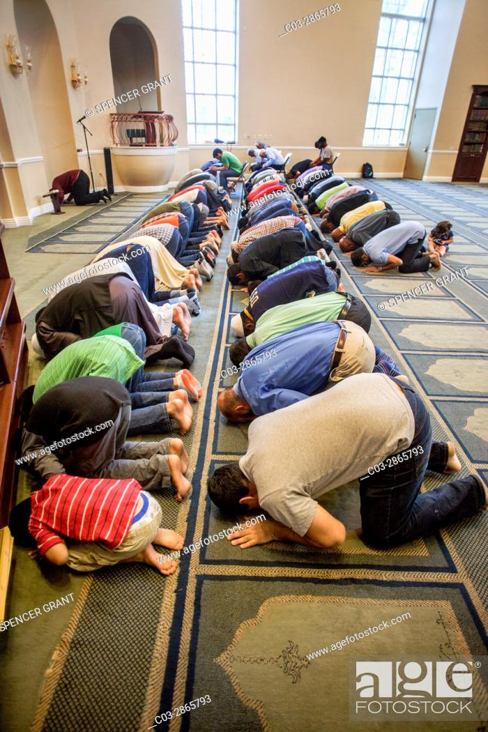 """Stock Photo: Muslim men prostrate themselves in """"""""Sujood"""""""" prayer position with their faces on the Islamic patterned carpet at Friday afternoon prayers during religious."""
