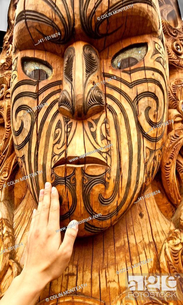 Stock Photo: Maori carving, a tourist's hand feels texture of face, Rotorua, New Zealand.