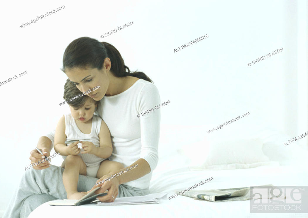 Stock Photo: Woman sitting on edge of bed with little girl on lap, looking down at agenda.