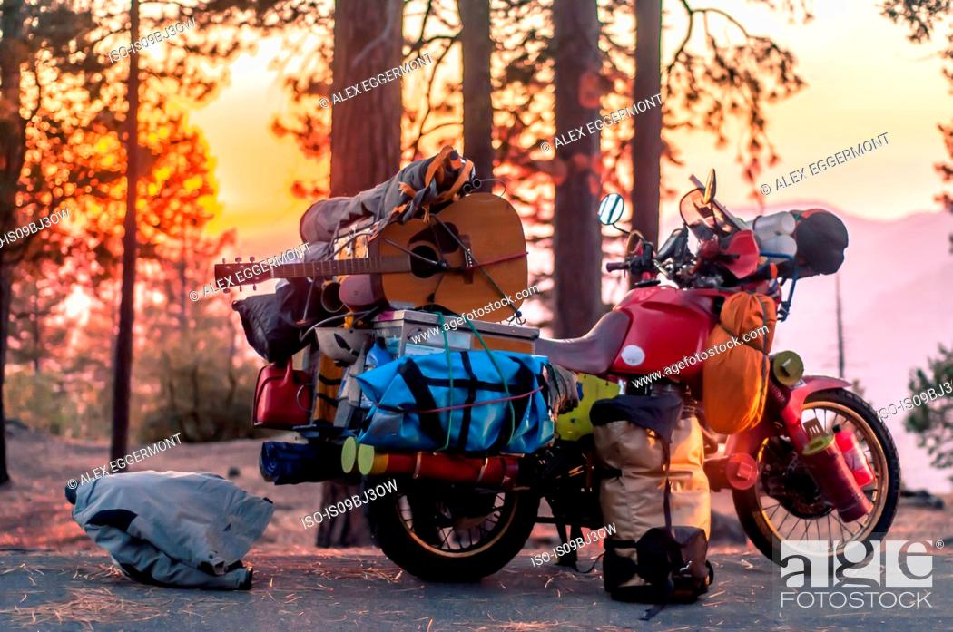 Imagen: Part unloaded touring motorcycle parked on forest roadside at sunset, Yosemite National Park, California, USA.