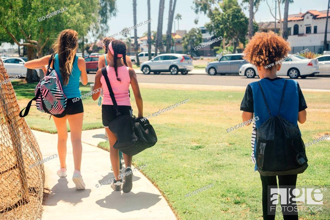 Stock Photo: Schoolgirls walking to soccer practice on school sports field.