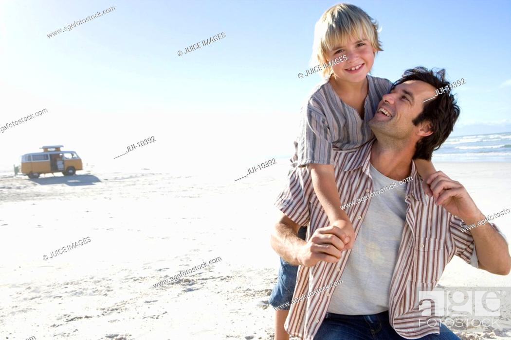 Stock Photo: Boy 6-8 on father's back on beach, smiling, portrait of boy.