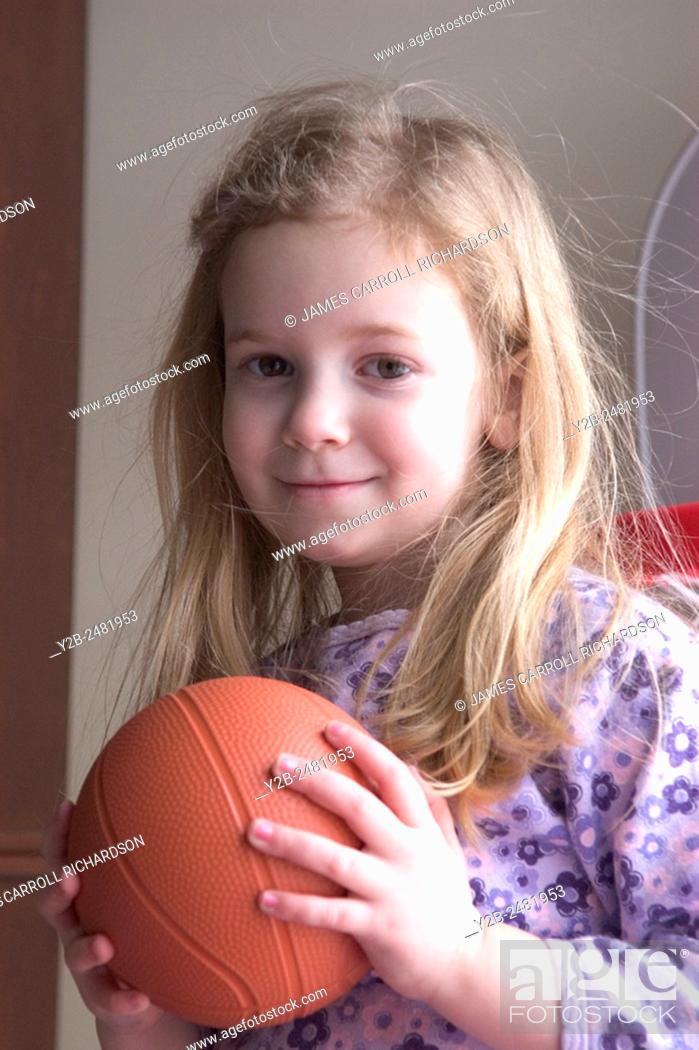 Stock Photo: Young girl with long blond hair smiles as she holds a small basketball.